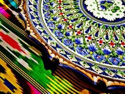 Uzbekistan ceramic plate & geometric decoration carpet - symbols of Uzbekistan Islamic culture. Detail of hand made knotted carpet, traditional flower elements patterned plate. Samarkand, Uzbekistan.
