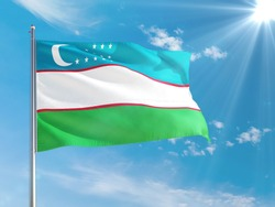 Uzbekistan national flag waving in the wind against deep blue sky. High quality fabric. International relations concept.