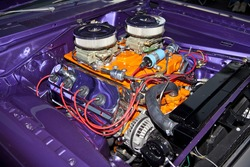 V-8 engine in a classic hot rod with dual carburetors and  painted in orange.
