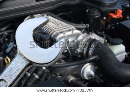 V8 Supercharged car engine and spanner. Focus on spanner. - stock photo