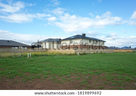 Photo of  Vacant land next to some residential suburban houses. Concept of real estate development, land for sale and a new suburb, Tarneit, Melbourne, VIC Australia.