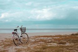 Vacant Spaces. Vintage Beach Cruiser Bike. Bicycle parked on beach. Retro bike near the sea. Bike on the background of the sea horizon.