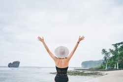 Vacation and freedom. Happy young woman rising hands up standing on tropical beach enjoying beautiful view.