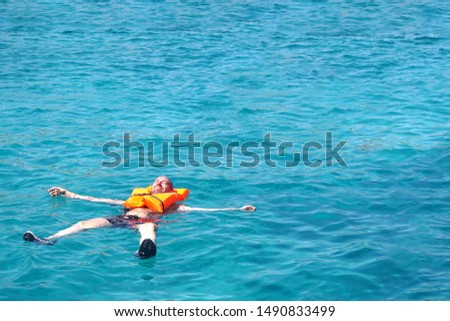 Vacation and relaxation concept, man floating relaxed on back in transparent pure blue sea water. Copy space.