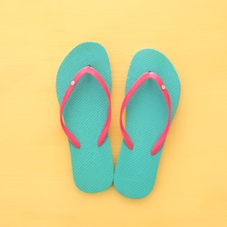 vacation and summer image with flipflops over yellow wooden background