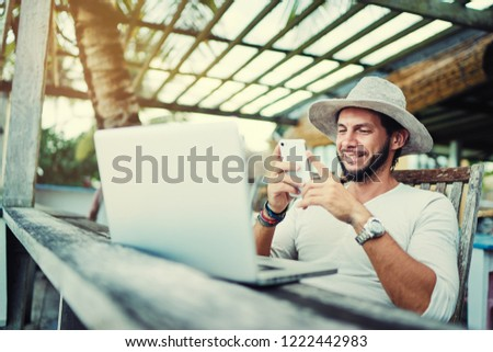 Vacation and technology. Work and travel. Young bearded man in hat using smartphone and laptop computer while sitting at beach cafe bar. #1222442983