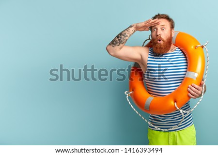 Vacation at sea and resort concept. Stupefied lifeguard with lifebuoy looks surprisingly into distance, notices someone who needs help, helps people being safe on water, supervises water from beach
