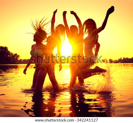 Vacation. Beach Party. Teenage girls having fun in water. Group of happy young people dancing at the beach on beautiful summer sunset. Silhouettes of group of teen girls jumping. Joyful friends