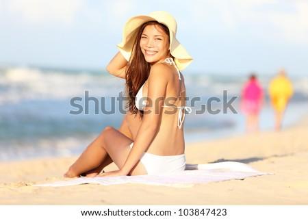 Vacation beach woman happy. Beautiful girl in bikini smiling in blissful joy at camera while sitting on beach on summer holidays travel. Pretty multiracial Caucasian / Asian Chinese model in bikini