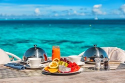 Vacation breakfast at luxury hotel room ocean view. Romantic honeymoon travel holiday in Maldives or Tahiti. Presentation of two plates, fruits, coffee, juice.