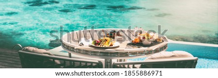 Vacation brunch food table at luxury restaurant hotel suite private terrace panoramic banner. Romantic cruise honeymoon travel destination holiday in Maldives or Tahiti.