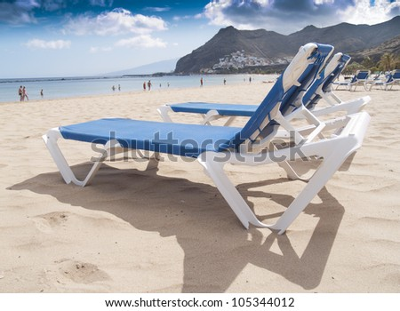 vacation concept: beach chairs on white sand on the shore of ocean