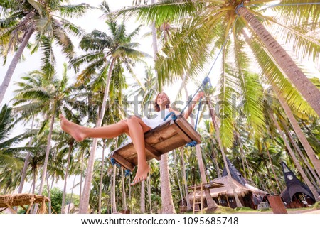 Vacation concept. Happy young woman in white dress swinging at palm grove. #1095685748