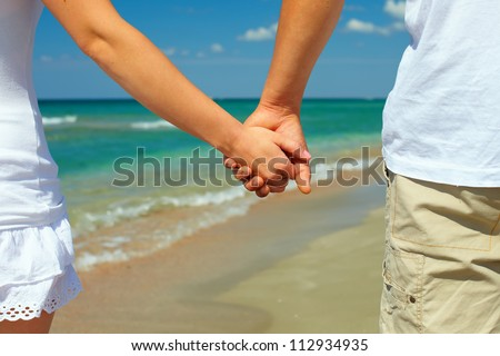 vacation concept, holiday romance. couple hands on sea shore background