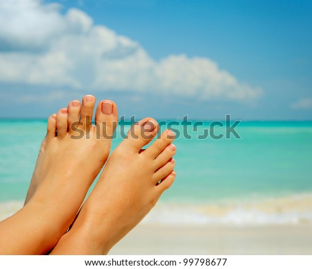 Vacation Concept. Tanning on the Beach. Woman's Bare Feet over Sea background