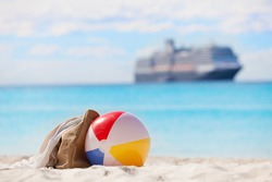 vacation concept, view of beach ball and beach bag at the sand with cruise ship in the background