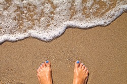 Vacation concept, women foot near sea foam, gold sand