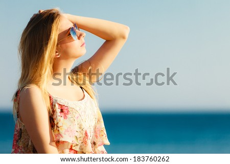 Vacation. Girl in summer dress and sunglasses standing on the empty beach. Young woman relaxing on the sea coast. Summertime. #183760262