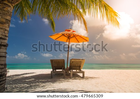 Vacation holidays background wallpaper - two beach lounge chairs under tent on beach in Maldives. #479665309