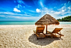 Vacation holidays background wallpaper - two beach lounge chairs under tent on beach. Sihanoukville, Cambodia
