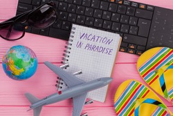 Vacation in Paradise on notebook with woman's traveler accessories glasses wallet and flip-flops on pink table top background. Globe black keyboard grey miniature airplane.