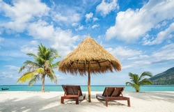 Vacation in tropical countries. Beach chairs, umbrella and palms on the beach.