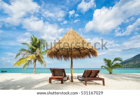Vacation in tropical countries. Beach chairs, umbrella and palms on the beach.  #531167029