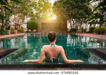 Vacation lifestyle scene of young woman sitting in swimming pool in morning time. Weekend and holiday lifestyle concept