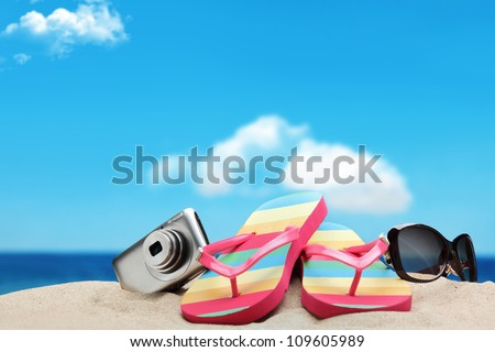 Vacation on beach, Camera,Flip-flops and Sunglasses on sand beach.