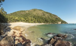 Vacation on the Meros(praia dos Meros) beach with clean sand, turquoise ocean water and blue sky with clouds on a sunny day. Panoramic view of the beach in Ilha Grande, south of Rio de Janeiro, Brazil