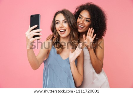 Vacation photo of two multiethnic brunette girls wearing dresses smiling and waving hand at camera while taking selfie on mobile phone isolated over pink background