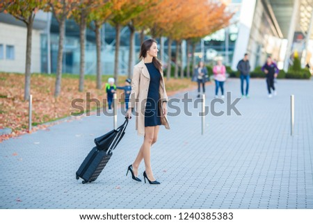 Vacation. Smiling female passenger proceeding to exit gate pulling suitcase through airport concourse.