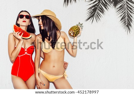 Vacation. Summer travel. Two beautiful sexy brunette girls outdoor with watermelon and pineapples in bikini on white wall background with palm tree shadow having fun laugh smile at the beach