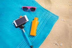 Vacation, technology and protection. Must have accessories on the sea beach. Smartphone, selfie stick, sunscreen and sunglasses. Top view.