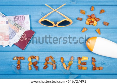 Vacation time concept. Inscription travel and shape of sun made of amber stones, passport with currencies euro, sunglasses and sun lotion #646727491