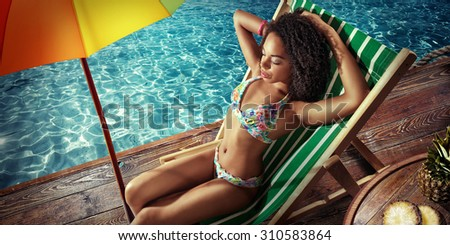 Vacation. Travel. Beautiful young woman relaxing on beach chair under umbrella. Top view