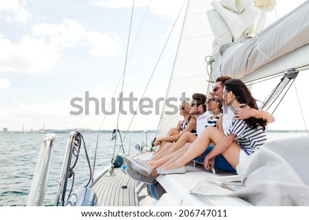 vacation, travel, sea, friendship and people concept - smiling friends sitting on yacht deck #206747011