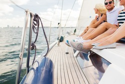 vacation, travel, sea, sailing and people concept - close up of friends legs sitting on yacht deck