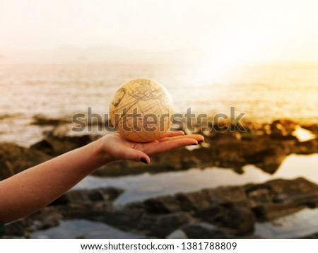Vacation travel summer weekend sea adventure trip concept. Vintage antique globe in hand on sea and rocks background. Copy space. Mock up for turism agency. Safe planet. Education and discovery idea