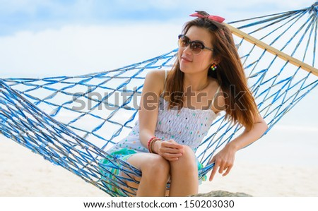 Vacation woman relaxing on beach in hammock on summer