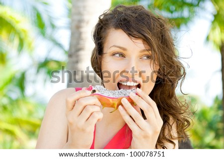 Vacation woman smiling on tropical beach summer holidays with palm trees. Portrait of pretty happy female model eating exotic Asian Dragon Fruit.