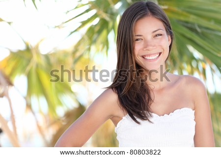 Vacation woman smiling on tropical beach summer holidays with palm trees. Portrait of pretty happy mixed race Caucasian / Asian female model.