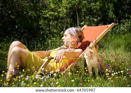 Vacation! Young woman sitting i a deck chair in the sun.