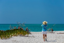Vacationer standing on white sand beach looking out over the ocean and the clear deep blue sky. Enjoying the beauty of nature's beaches.