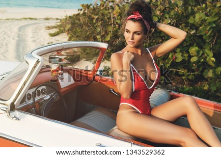 Vacations in Cuba. Sexy woman wearing red swimsuit in retro cabriolet car on the beach.