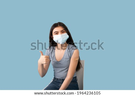 Vaccinated teen girl in face mask showing plaster bandage on her arm after getting covid-19 vaccine injection on blue studio background. Coronavirus population immunization campaign