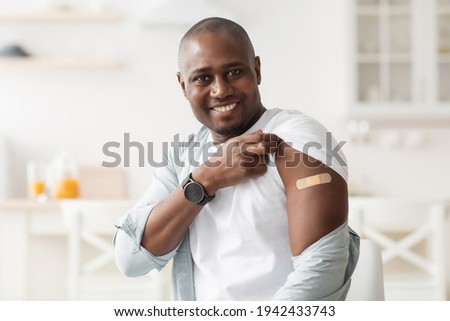 Vaccination concept. Happy african american man holding up shirt sleeve showing plaster after coronavirus vaccine Сток-фото ©