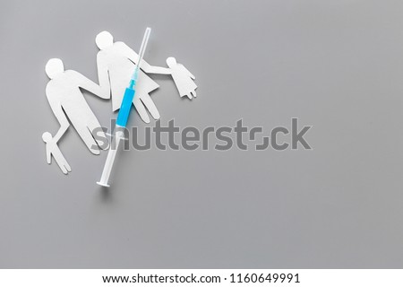 Vaccination for healthy family, vacctination of children. Flu. Syringe near family cutout on grey background top view copy space