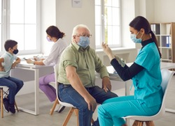 Vaccination for people of different ages. Asian doctor giving flu or pneumonia shot to senior man in face mask. Elderly patient, being in risk group, receiving Covid-19 vaccine in modern clinic office
