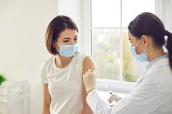 Vaccination, immunization, disease prevention concept. Doctor disinfects skin on patient's arm before giving injection. Young woman in medical face mask getting Covid-19 or flu vaccine at the clinic